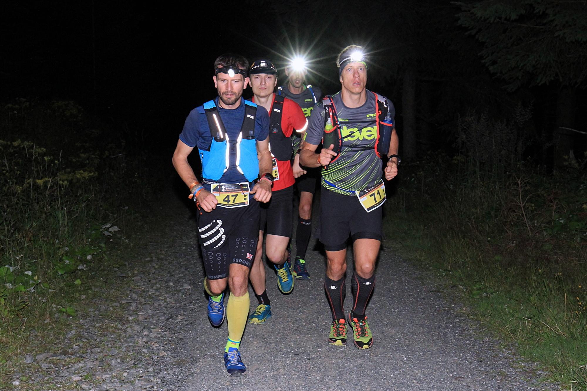 Skupina běžců v noci.